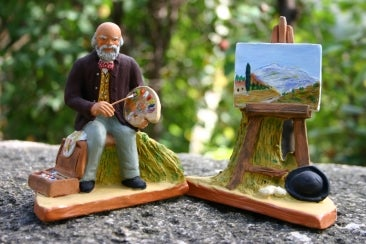 Artist with white beard at his easel with a view of snow-covered mountain