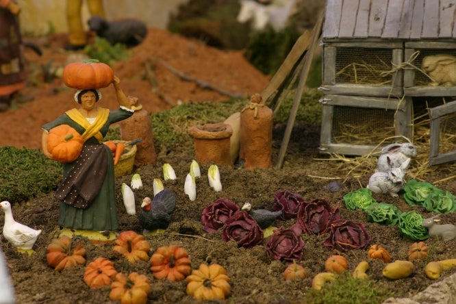 Provençal Santon of a woman carrying pumpkins from her potager garden, with other vegetables, cabbage and endives, and a shed in background