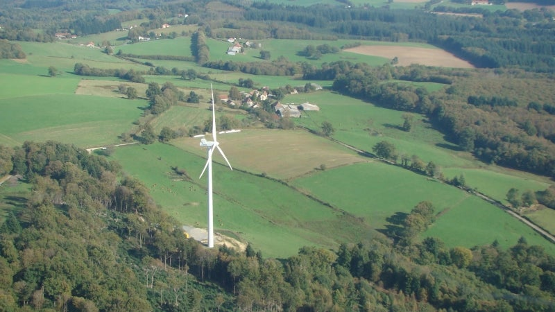 A wind turbine on the side of a hill in rolling country